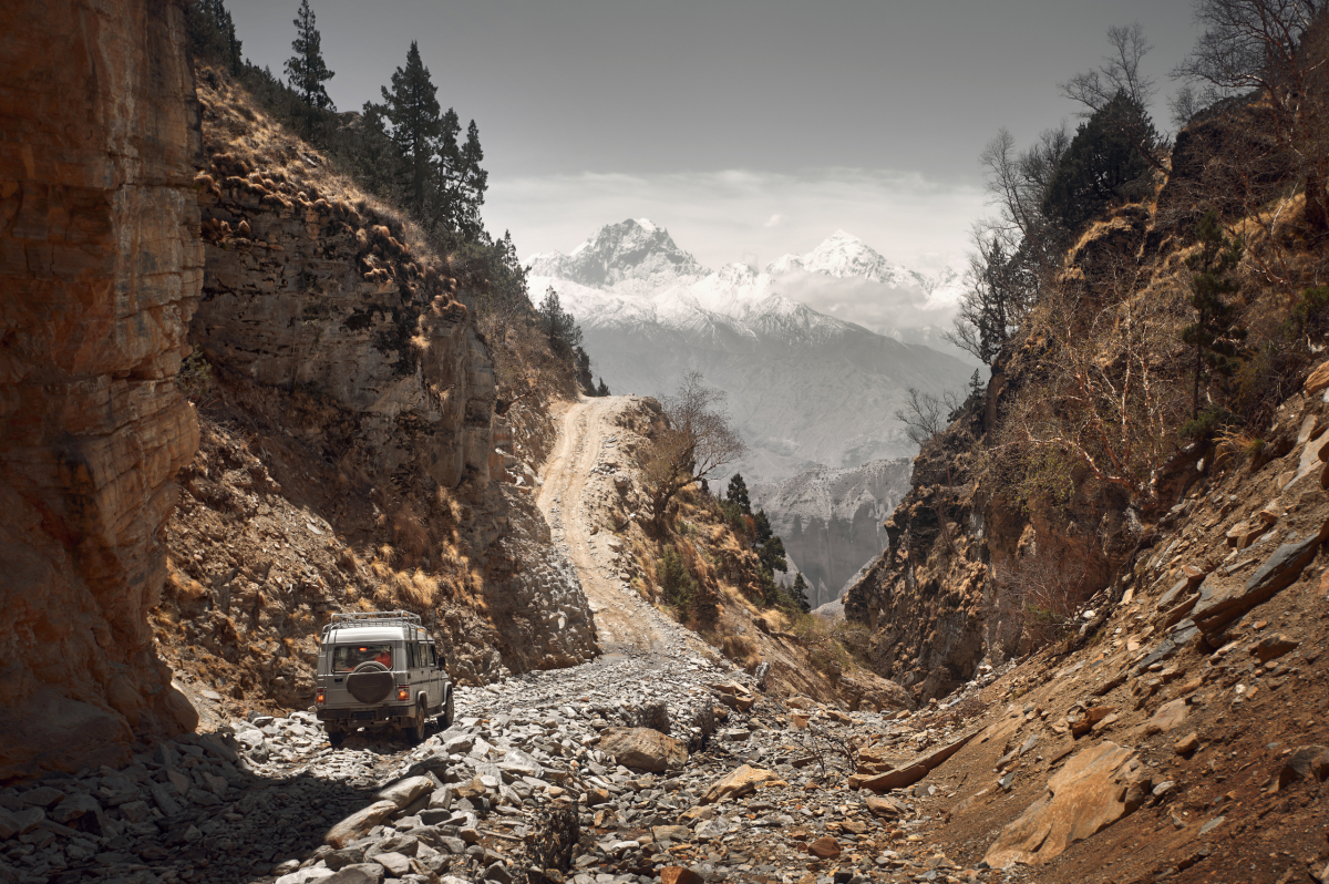 Off-road vehicle goes an extreme mountain path during an expedition to Himalayas